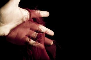 A human hand holds a fraying, spooled piece of red silk