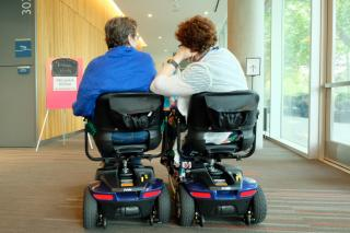 Two women on accessibility scooters, pictured from behind, are pulled up close together and talking in a hallway.