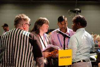 A small group of delegates and officials gather in discussion near the amendment microphone in General Session