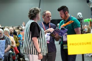 Two delegates consult the GA agenda book near the Procedure microphone, while a volunteer teller in a striped vest looks on