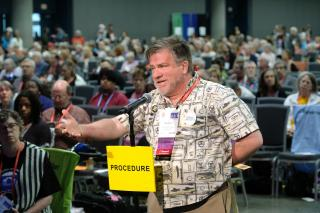 A delegate gestures widely while speaking at the Procedure microphone in General Session