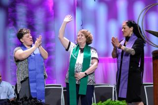 Three GA Chaplains are acknowledged on stage; the middle chaplain, wearing a green stole, waves to the audience