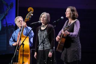 A cellist, a vocalist, and a guitar player perform on stage together.