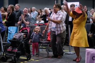 A family dances together in the aisle of the main hall, during worship