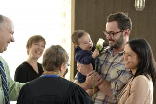 A baby holding a white rose is surrounded by smiling adults at a UU child dedication.