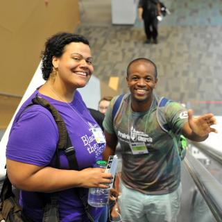 Lena K Gardnerin purple and Kenny Wiley in green are smiling up at the camera while riding up an escalator.