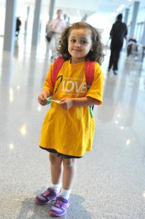 A young girl with brown curly hair is pictured wearing purple sneakers and a yellow Stand With Love campaign t-shirt.