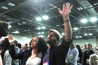 Two worship attendees stand arm in arm, with other hands raised.