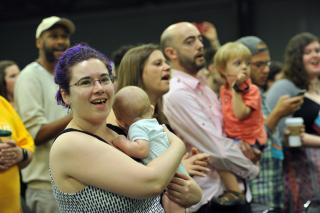 A singing audience includes a purple-haired mother holding an infant, and a bearded man holding a toddler.