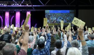 Delegates, from behind are pictured holding their voting cards aloft during a vote in general session.