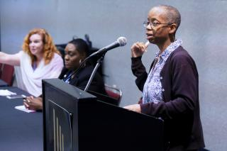 An African-American workshop leader speaks at a lectern.
