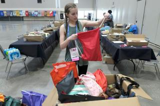 A GA attendee with two long braids pulls a red cinch backpack from a box of donated bags.