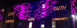 UU Value words, Love, Justice, Hope, Faith and Community, projected on to a building for light show.