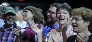 People clap and sing at a worship service at General Assembly