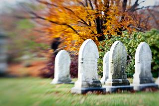 Against a blurred background of fall foliage, several old gravestones on a cemetery lawn.