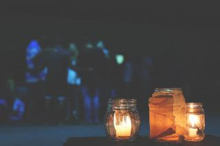 In the foreground, a trio of candles in small jars. In the background, a group of people form a friendly huddle.