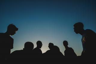 A half-dozen people (heads and shoulders) silhouetted against a deep blue sky.