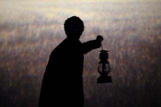 "In front of a wheatfield backdrop, the silhouette of a person holding up an old-fashioned lantern (from a 2011 production of ""The Wizard of Oz"")"