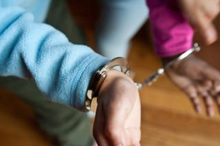 handcuffs restrain the wrists of a person of color