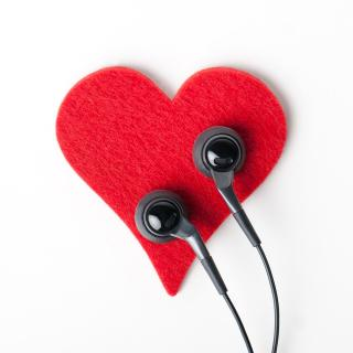 A red felt heart with earbuds laying on top
