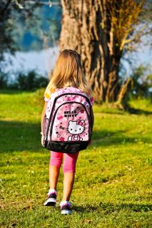 A young girl wears a large pink Hello Kitty backpack, in this photo taken from behind.