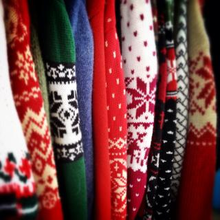 An assortment of brightly colored holiday sweaters, in profile, lined up as they hang together