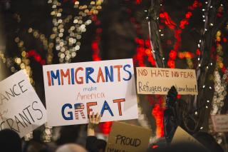 "At a rally or protest, signs held in the air say ""Immigrants make America great"" and ""No hate, No fear, refugees are welcome here."""