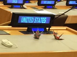 Two Japanese origami cranes placed behind the United States' nameplate during the UN negotiations for a Treaty to ban nuclear weapons.