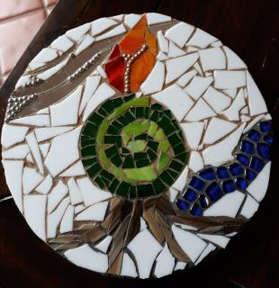 A round mosaic with tree roots, a flame, and a green spiral.
