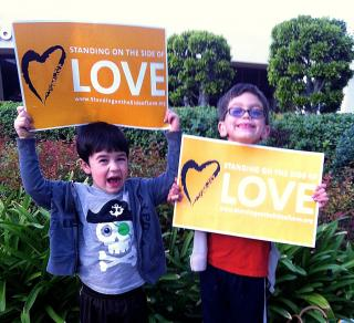 Children, smiling, hold signs for the Standing on the Side of Love campaign.