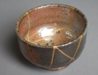 A pottery bowl with seams of gold showing where it's been made whole after breaking