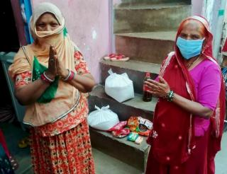 Two women wearing face coverings working to deliver supplies during the COVID-19 pandemic