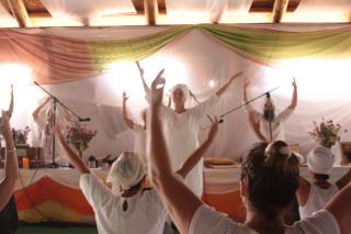Several Kundalini practitioners, dressed in white, lift their arms as they chant