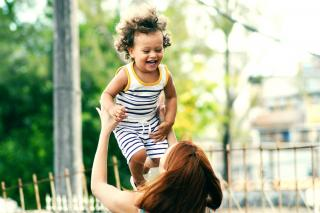 A toddler laughs, mid air, as an adult lifts the toddler into the air.