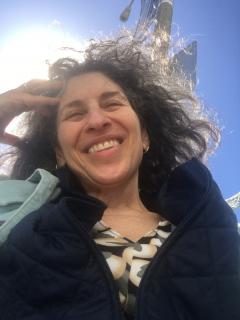 This is a shoulders-up photo of Susan Dana Lawrence, a white woman with salt and pepper wavy hair, smiling into the sun. She is wearing a print shirt, a black sweater, and light blue, collared jacket.