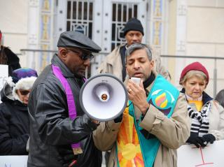 Rev. Manish Mishra-Marzetti leads prayer with a bullhorn at a Black Lives Matter event.