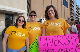 "Three members of the Huntsville, AL Unitarian Universalist congregation at a Women's March, wearing Standing on the Side of Love tee shirts and holding a sign that says ""Diversity Makes America Great"""