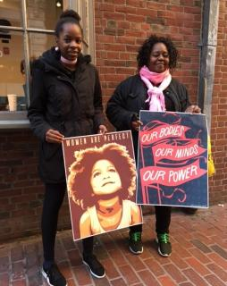 "Two black women display artful signs they carried at the Boston Women's March. One shows a young African American girl and the message ""Women are perfect."""