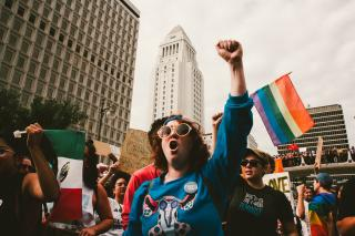 With buildings behind them, people march in Los Angeles holding the rainbow and Mexican flags. The woman in the center of the photo is raising her vist, mid-chant.