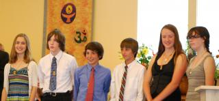 Six youth pose wearing flaming chalice pendants after their Coming of Age service.