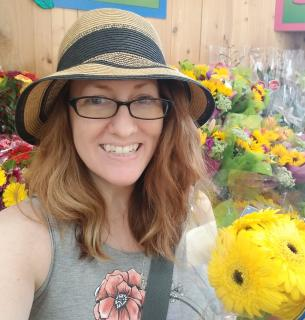 Monica Dobbins in a straw hat, holding flowers, with racks of sunflowers behind her.