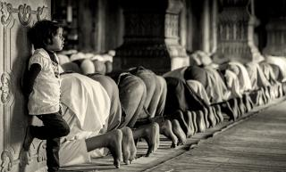 A child, lost in thought, leans against a pillar next to a row of Muslims bowing in prayer in a mosque