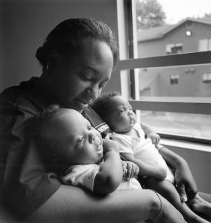 An African-American mother cradles her infant twins, one in each arm, as the babies gaze out of a window.