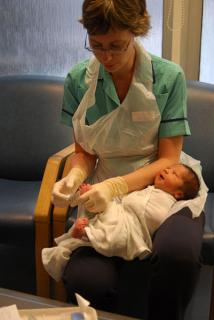 A nurse with a swaddled newborn baby cradled in her lap
