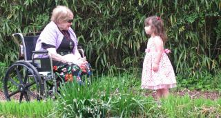 Woman in colorful skirt in wheelchair with young girl in pink dress amid green plants.