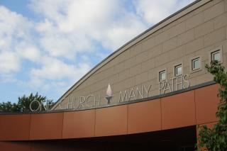 "The outside of a UU congregation's building, reading ""One Church Many Paths"""
