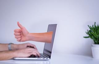 "laptop with a hand coming out with a ""thumbs up"""