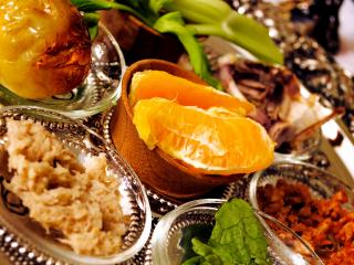 A prepared seder plate with orange slices in the center.