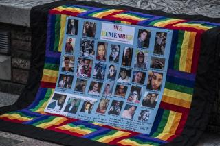 a small rainbow quilt is draped on steps, with a mosaic of photos of the victims of Orlando's shooting