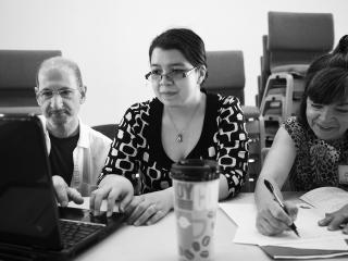 Three people at a table with a coffee cup and a laptop computer.